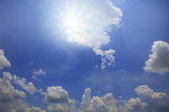 发光在与白色云彩天光的蓝天的太阳 库存照片