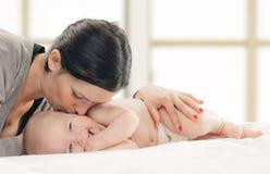 婴孩面颊愉快的亲吻的母亲 库存照片