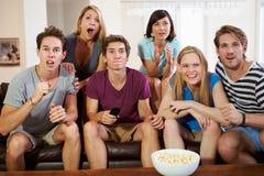 朋友坐沙发一起看电视的小组 免版税库存图片