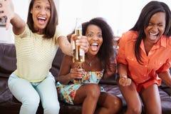 妇女坐沙发一起看电视的小组 库存照片