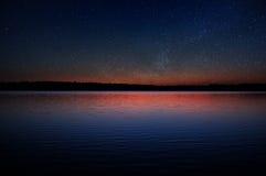 在镇静湖的日落有在黑暗的天空的真正的星的 库存照片