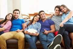 朋友坐沙发一起看电视的小组 图库摄影