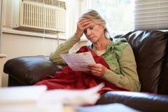 担心的资深妇女坐看票据的沙发 库存照片