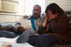 担心的资深夫妇坐看票据的沙发 免版税库存照片