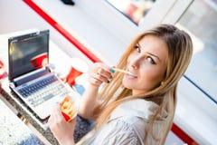 坐在桌在餐馆或与吃可口油炸物的便携式计算机的咖啡店上的美丽的白肤金发的年轻女商人 免版税库存图片
