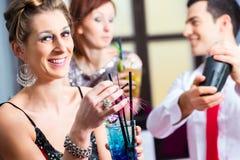 在鸡尾酒酒吧的妇女饮用的鸡尾酒 免版税库存图片