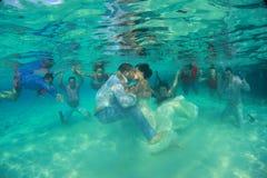 与许多夫妇的新娘和新郎亲吻的水中在背景中 免版税图库摄影