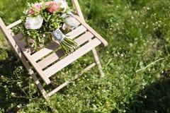 在椅子的婚礼花束 免版税库存图片