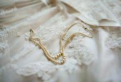 与珍珠的婚礼礼服细节 免版税库存照片