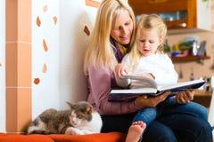 母亲读书在家哄骗的夜故事 免版税库存照片