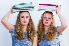 有课本的两位女小学生在他们的头 免版税库存图片