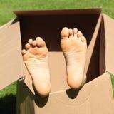 在箱子的儿童脚 免版税库存图片