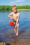 有一个桶的男孩水 免版税库存图片