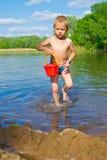 有一个桶的男孩水 免版税库存照片