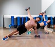 哑铃在健身健身房的俯卧撑夫妇 免版税库存照片