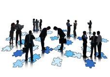 小组研究和站立七巧板的商人 免版税库存图片