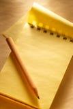 Прикройте открытый желтый блокнот с карандашем Стоковые Изображения RF