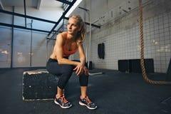 采取休息的女运动员在行使以后在健身房 库存图片