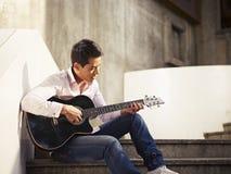 Κιθάρα νεαρού παιχνιδιού άνδρων και τραγούδι Στοκ Εικόνες