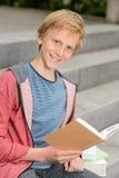 学习坐台阶的愉快的十几岁的男孩 免版税库存照片