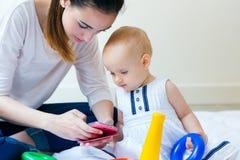 母亲和在家使用智能手机的女婴 免版税图库摄影