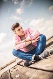 Καθισμένος νεαρός άνδρας που το χείλι του Στοκ Φωτογραφίες
