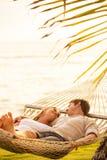 放松在热带吊床的夫妇 免版税库存照片