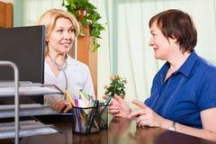 正面医生谈话与他的患者 免版税库存照片