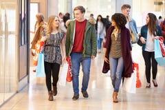 一起购物在购物中心的小组年轻朋友 免版税图库摄影
