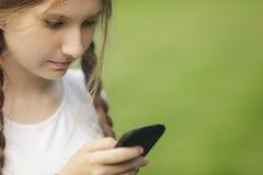 使用手机的青少年的女孩 免版税库存照片