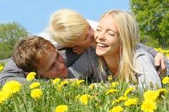 拥抱和亲吻在花草甸的母亲、父亲和孩子 免版税库存图片