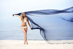 年轻人、适合和美丽的妇女海滩跳舞的与丝绸 免版税库存图片