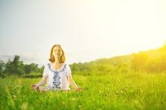 做在绿草的少妇瑜伽 免版税库存图片