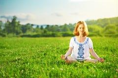 做在绿草的少妇瑜伽 库存照片
