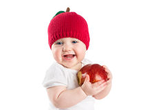 一个被编织的苹果帽子的逗人喜爱的婴孩咬住在一个红色成熟苹果的,隔绝在白色 库存照片