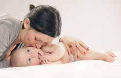 婴孩面颊愉快的亲吻的母亲 免版税库存图片