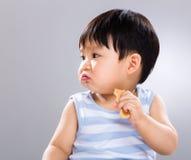 Το μικρό παιδί τρώει το μπισκότο και κοιτάζει κατά μέρος Στοκ Εικόνες