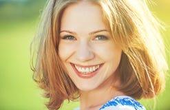笑和微笑在自然的愉快的美丽的少妇 免版税库存图片