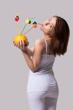秀丽妇女站立和从橙汁的饮料与秸杆 免版税库存照片