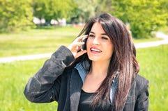 年轻女商人在有智能手机的公园 库存照片