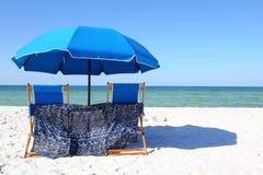 两张海滩睡椅在一个白色沙滩的一把蓝色伞下 库存照片