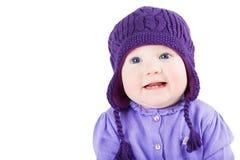 有戴一个紫色毛线衣和被编织的帽子的蓝眼睛的美丽的女婴 免版税库存图片
