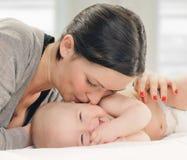 婴孩面颊愉快的亲吻的母亲 免版税库存照片