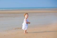 使用在一个美丽的热带海滩的逗人喜爱的卷曲女婴 免版税库存图片