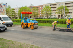 压路机和沥青铺的机器在街道上 库存照片