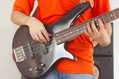 夸大低音吉他关闭的吉他弹奏者的手 免版税库存图片