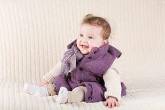 紫色夹克的逗人喜爱的笑的女婴在编织 免版税库存图片
