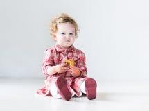 穿红色礼服的滑稽的女婴吃圣诞节饼 免版税库存照片
