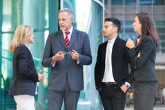 Группа в составе бизнесмены говоря внешняя Стоковое Изображение RF