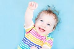 蓝色背景的滑稽的愉快的女婴 图库摄影